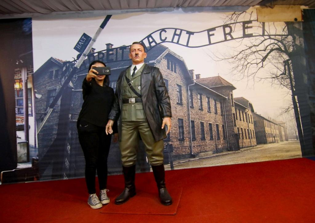 An Indonesian woman take a selfie with a life-size wax sculpture of Adolf Hitler at a museum in Yogyakarta