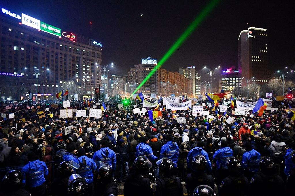 Riot police stand guard as people demonstrate in Bucharest, on February 1, 2017 against controversial decrees to pardon corrupt politicians and decriminalize other offenses in front of the government headquarters (AFP Photo/Daniel MIHAILESCU)