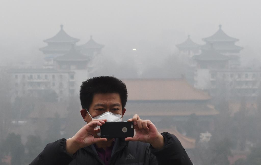 A visitor takes photos in Jingshan park as pollution levels soared above safe levels in Beijing (AFP Photo/Greg Baker)
