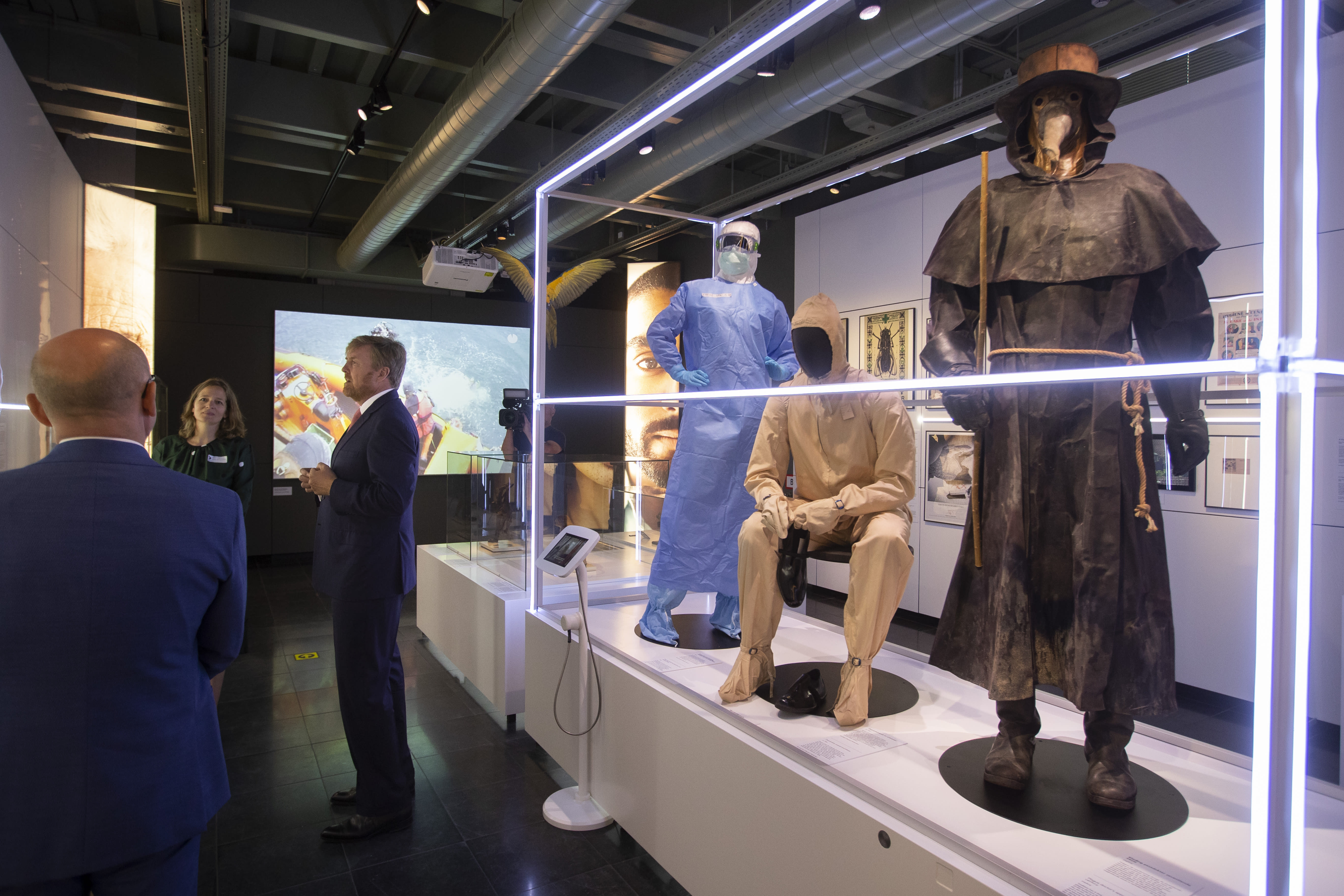 """Dutch King Willem-Alexander, center, curator Mieneke te Hennepe, second left, and director Amito Haarhuis, left, tour the """"Contagious!"""" exhibit at Rijksmuseum Boerhave in Leiden, Netherlands, Thursday, July 16, 2020. The museum finally opened an exhibition Thursday on contagious diseases through the ages after a long delay caused by the disease currently sweeping the world, COVID-19. (AP Photo/Peter Dejong, Pool)"""