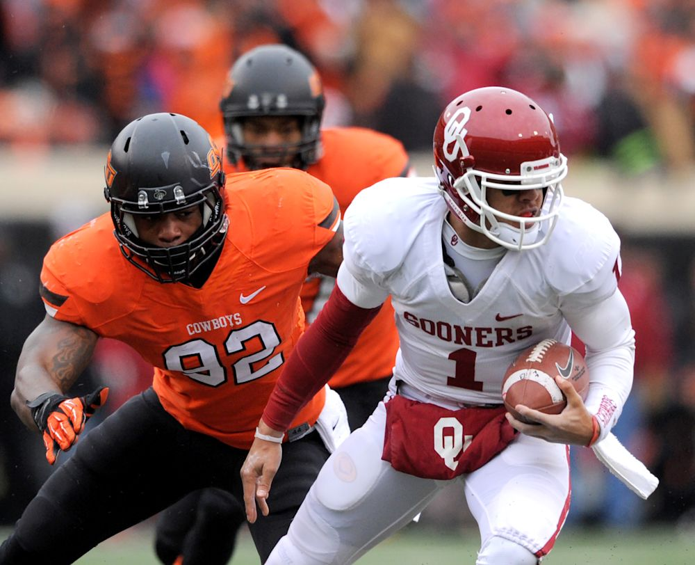 Oklahoma State defensive end Jimmy Bean, left, reaches for Oklahoma quarterback Kendal Thompson during the first half of an NCAA football game in Stillwater, Okla., Saturday, Dec. 7, 2013. Thompson had 17 yards passing in the 33-24 win over rival Oklahoma State