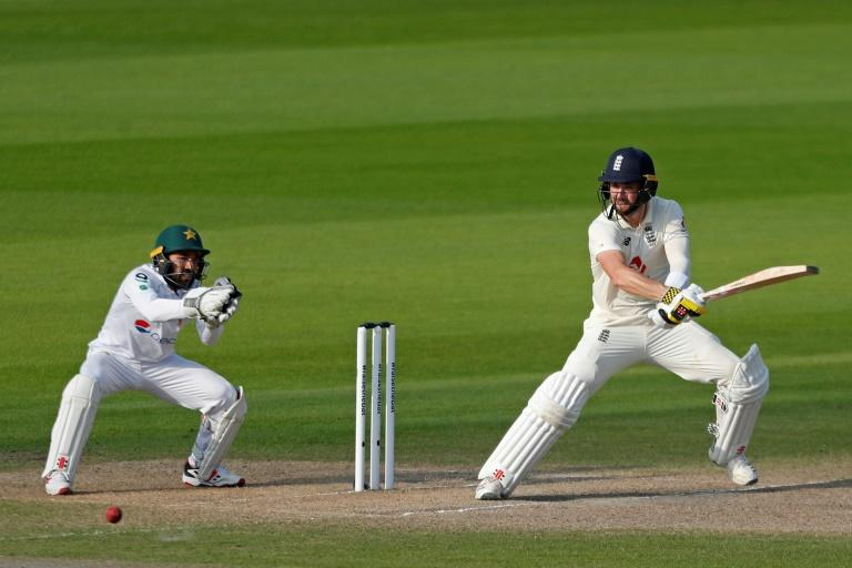 Cut above - England's Chris Woakes on his way to a match-winning 84 not in the first Test at Old Trafford as Pakistan wicketkeeper Mohammad Rizwan looks on
