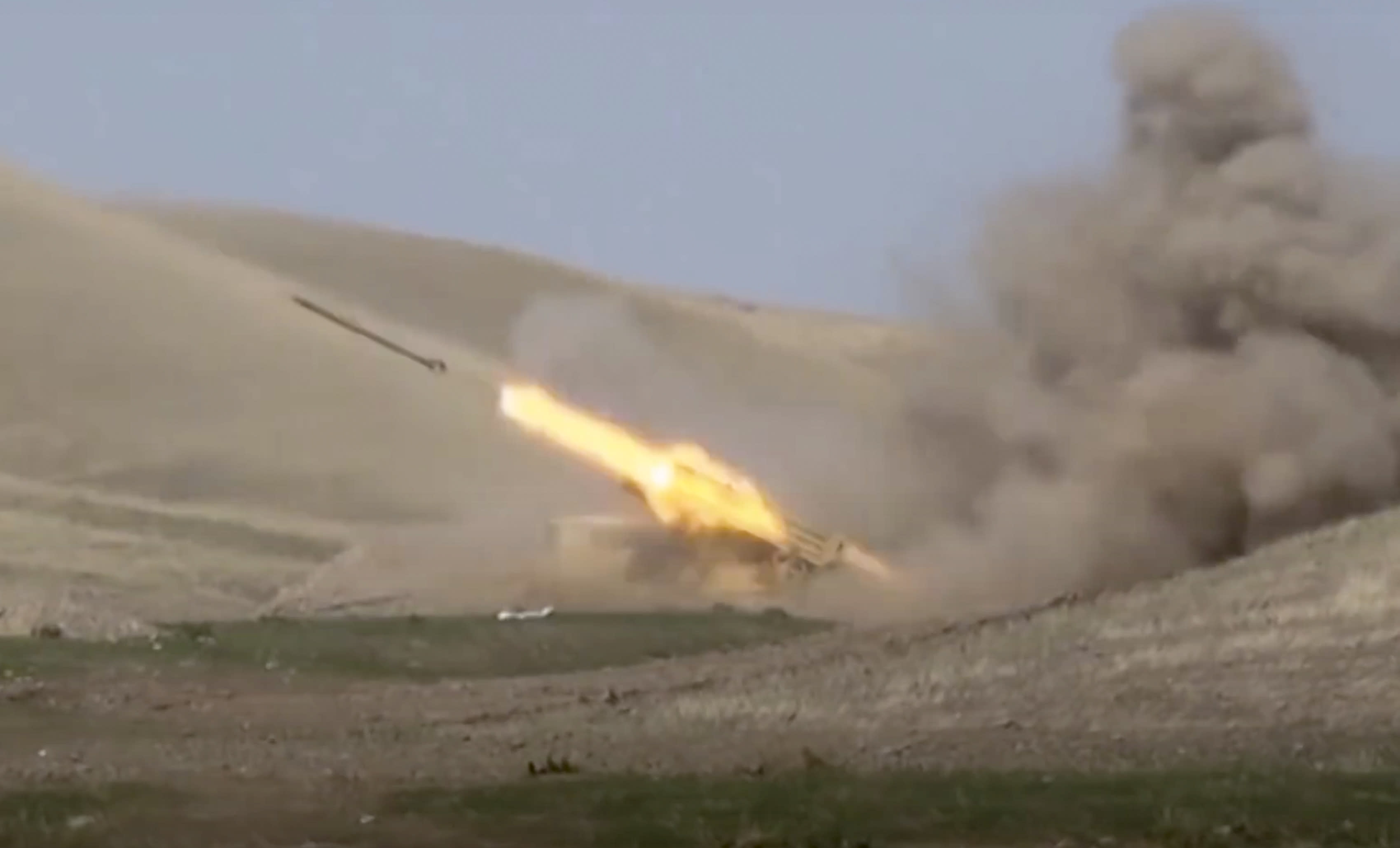 In this image taken from footage released by Azerbaijan's Defense Ministry on Sunday, Sept. 27, 2020, an Azerbaijan's rocket launches from missile system at the contact line of the self-proclaimed Republic of Nagorno-Karabakh, Azerbaijan. Fighting between Armenian and Azerbaijani forces over the disputed separatist region of Nagorno-Karabakh continued on Monday morning after erupting the day before, with both sides blaming each other for resuming the attacks. (Azerbaijan's Defense Ministry via AP)