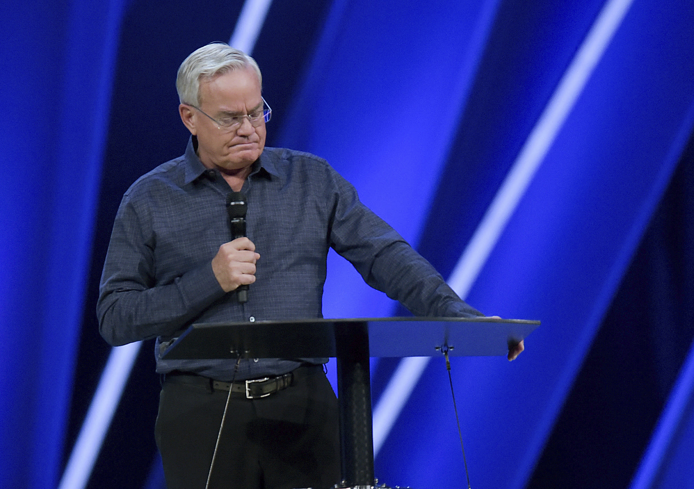 FILE - In this Tuesday, April 10, 2018 file photo, Willow Creek Community Church Senior Pastor Bill Hybels stands before his congregation in South Barrington, Ill., where he announced his early retirement effective immediately, amid a cloud of misconduct allegations involving women in his congregation. The announcement was made during a special meeting at the church, one of the nation's largest evangelical churches, which he founded. (Mark Black/Daily Herald via AP)