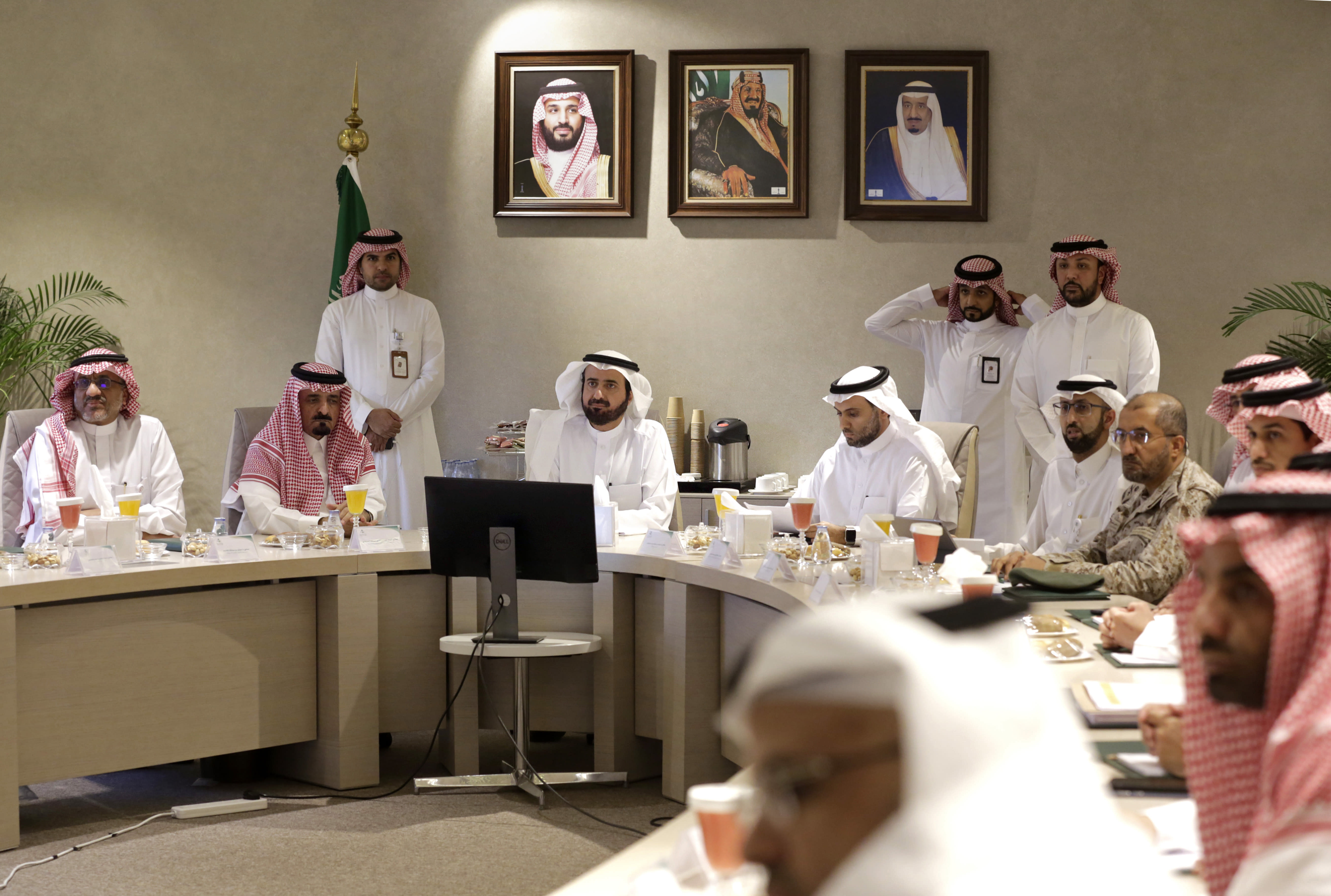 Saudi Health Minister Tawfiq Al-Rabiah, center left, meets with health officials to discuss the latest situation on coronavirus, at the Saudi Food and Drug Authority in Riyadh, Saudi Arabia, Thursday, Feb. 27, 2020. Saudi Arabia halted travel to the holiest sites in Islam over fears of the global outbreak of the new coronavirus just months ahead of the annual hajj pilgrimage. At top photos show Saudi King Salman, right, his Crown Prince Mohammed bin Salman, left, and Saudi Arabia's founder late King Abdul Aziz Al Saud. (AP Photo/Amr Nabil)