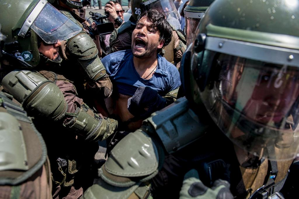 A Mapuche demonstrator is arrested by the Chilean riot police during a protest in Santiago against the death of 24-year-old Camilo Catrillanca (AFP Photo/Martin BERNETTI)