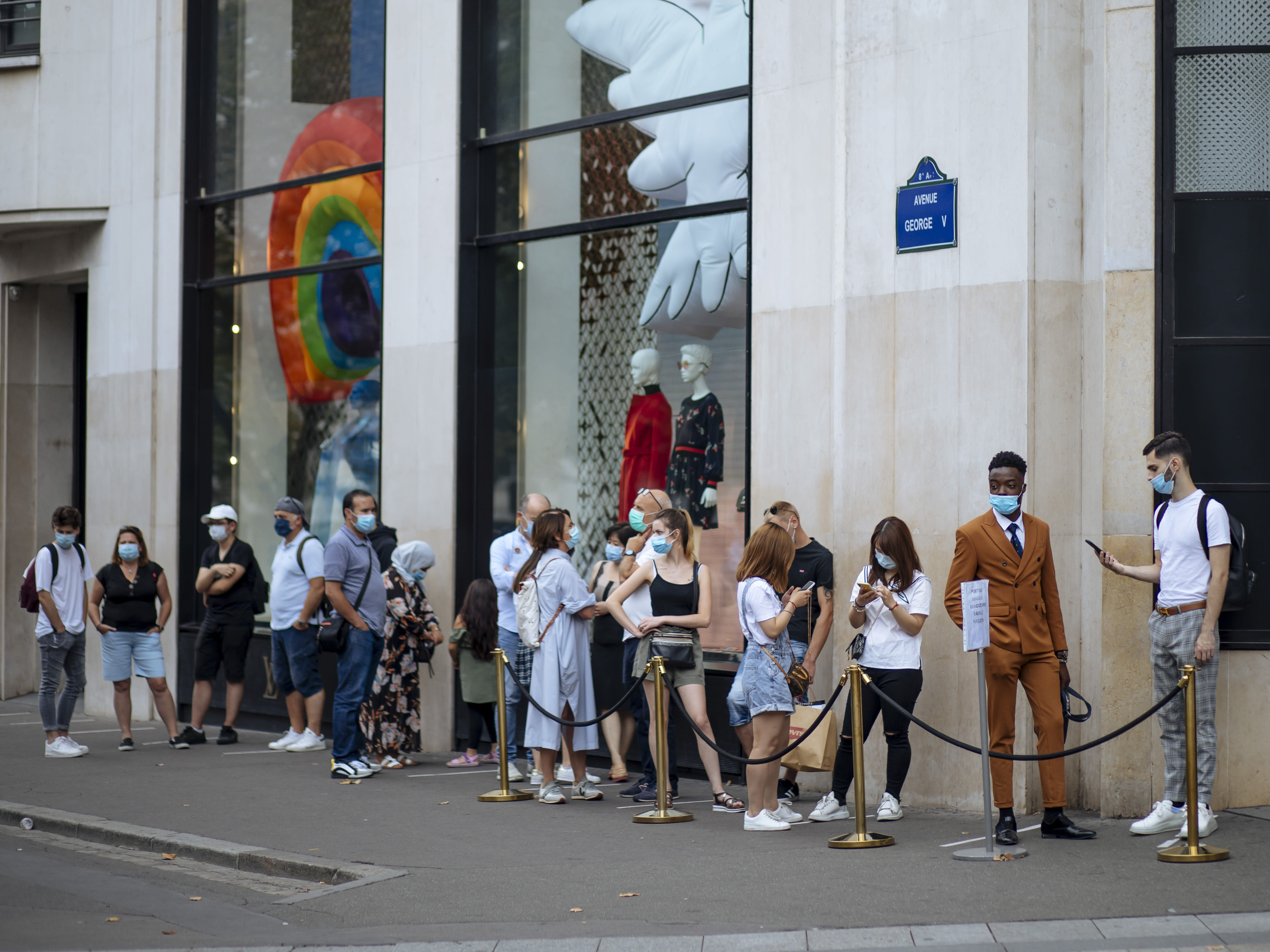 """People with face masks queue as they wait to get in the Louis Vuitton shop on the Champs Elysee avenue in Paris, Saturday, Aug. 15, 2020. Paris extended the areas of the city where pedestrians will be obliged to wear masks starting Saturday morning after health officials said that the coronavirus is """"active"""". The Champs-Elysees Avenue and the neighbourhood around the Louvre Museum are among zones where masks will be obligatory. (AP Photo/Kamil Zihnioglu)"""