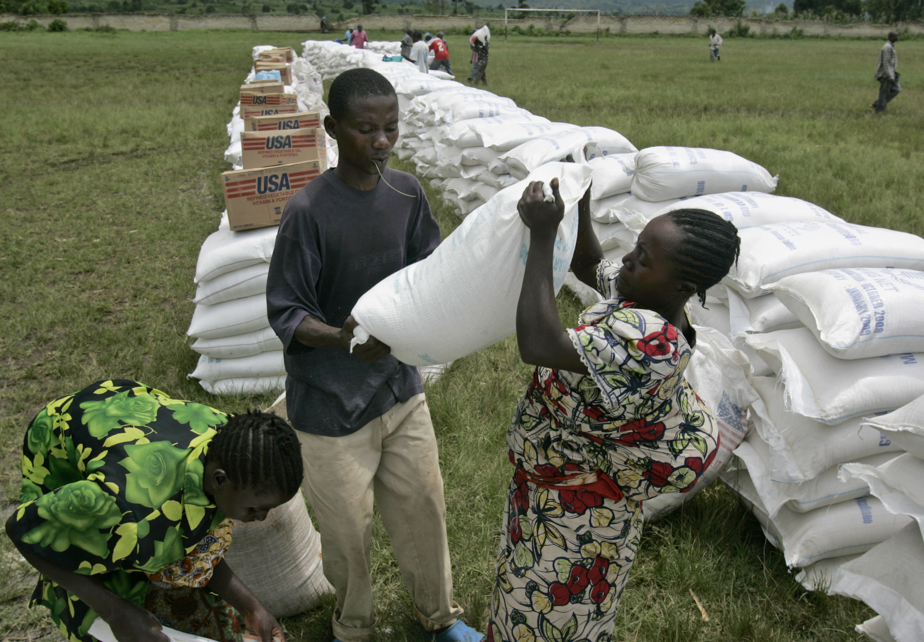 In this Nov. 14, 2008, file photo, a woman receives a bag of maize meal from the World Food Program in the town of Rutshuru, eastern Congo. The World Food Program chief warned Thursday, Sept. 17, 2020, that millions of people are closer to starvation because of the deadly combination of conflict, climate change and the COVID-19 pandemic and he urged donor nations and billionaires to help feed them and ensure their survival. (AP Photo/Karel Prinsloo)