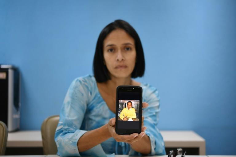 Venezuelan Mirian Gamarra, 39, displays a picture of her dead son Luis Alfredo Ariza, 21, on her mobile phone -- she says he was gunned down by special police for no reason (AFP Photo/STR)