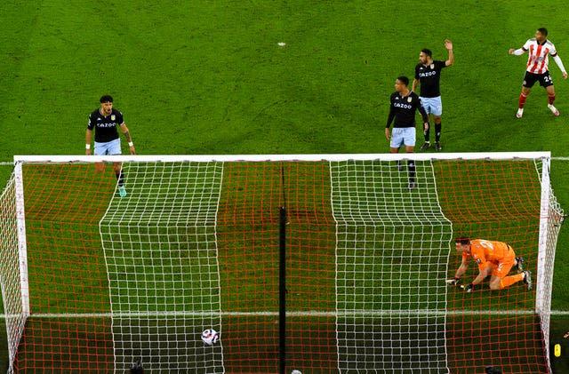 Aston Villa goalkeeper Emiliano Martinez (bottom right) looks on as Sheffield United's David McGoldrick scores