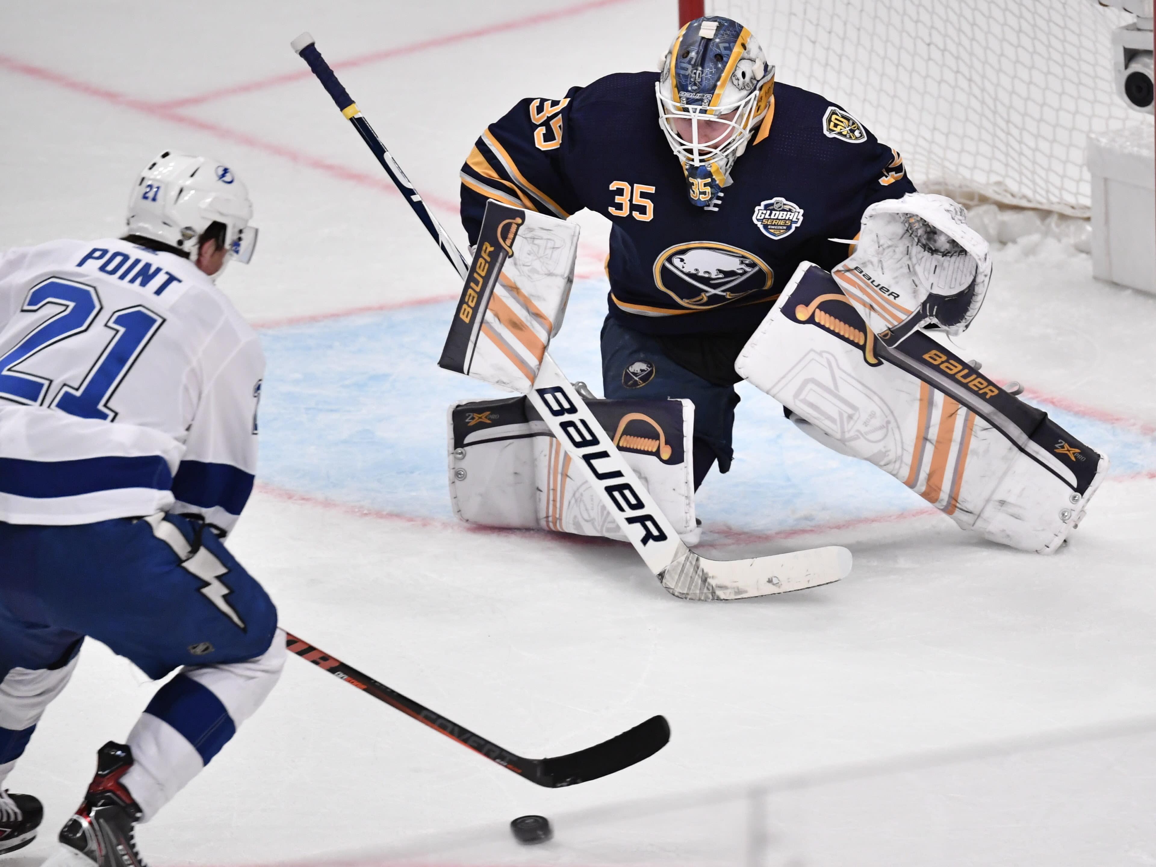 Tampa Bay Lightning Brayden Point (21) take a shot as Buffalo Sabres' goalie Linus Ullman defends during an NHL hockey game in Globen Arena, Stockholm Sweden. Friday. Nov. 8, 2019. (Anders Wiklund/TT via AP)