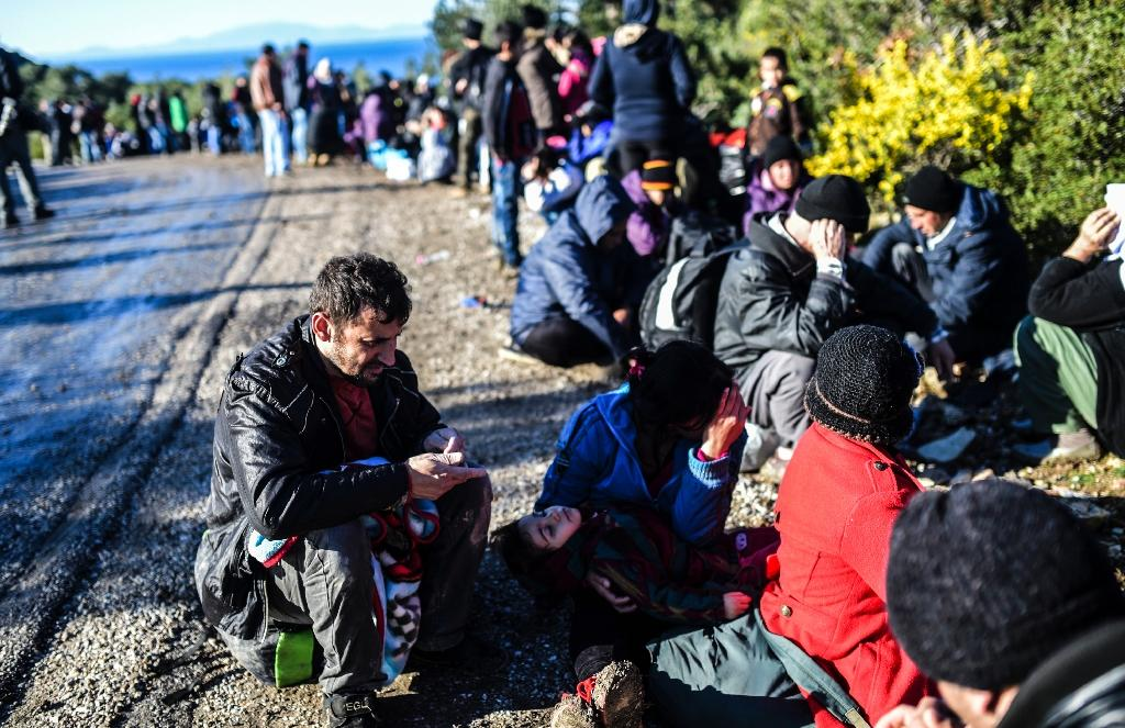 Migrants wait at the side of the road after being detained by Turkish soldiers as they try to reach the Greek island of Lesbos from Dikili, western Turkey, on March 5, 2016 (AFP Photo/Bulent Kilic)