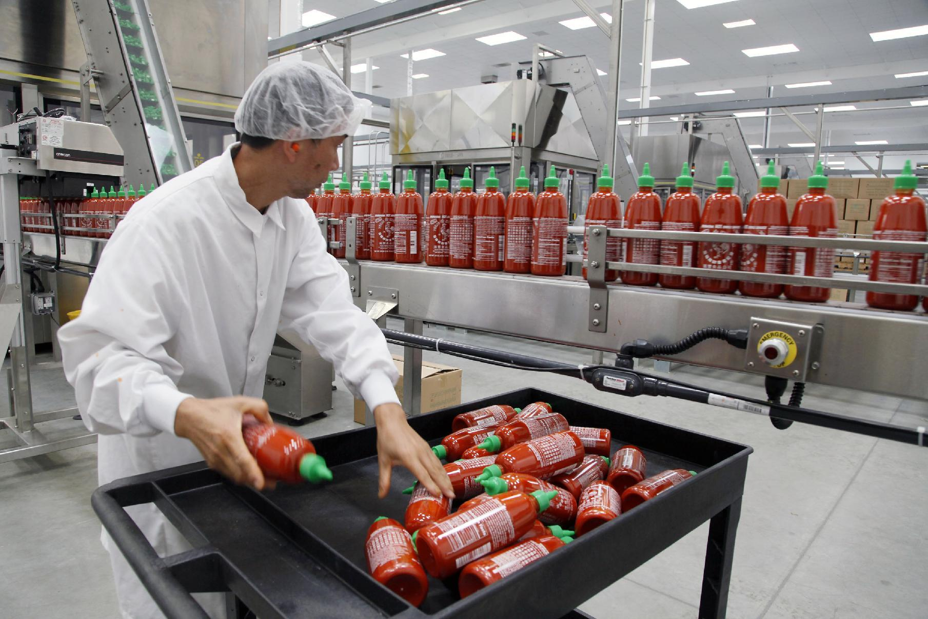 Sriracha chili sauce is produced at the Huy Fong Foods factory in Irwindale, Calif., on Tuesday, Oct 29, 2013. The maker of Sriracha hot sauce is under fire for allegedly fouling the air around its Southern California production site. The city of Irwindale filed a lawsuit in Los Angeles Superior Court Monday asking a judge to stop production at the Huy Fong Foods factory, claiming the chili odor emanating from the facility is a public nuisance. (AP Photo/Nick Ut)