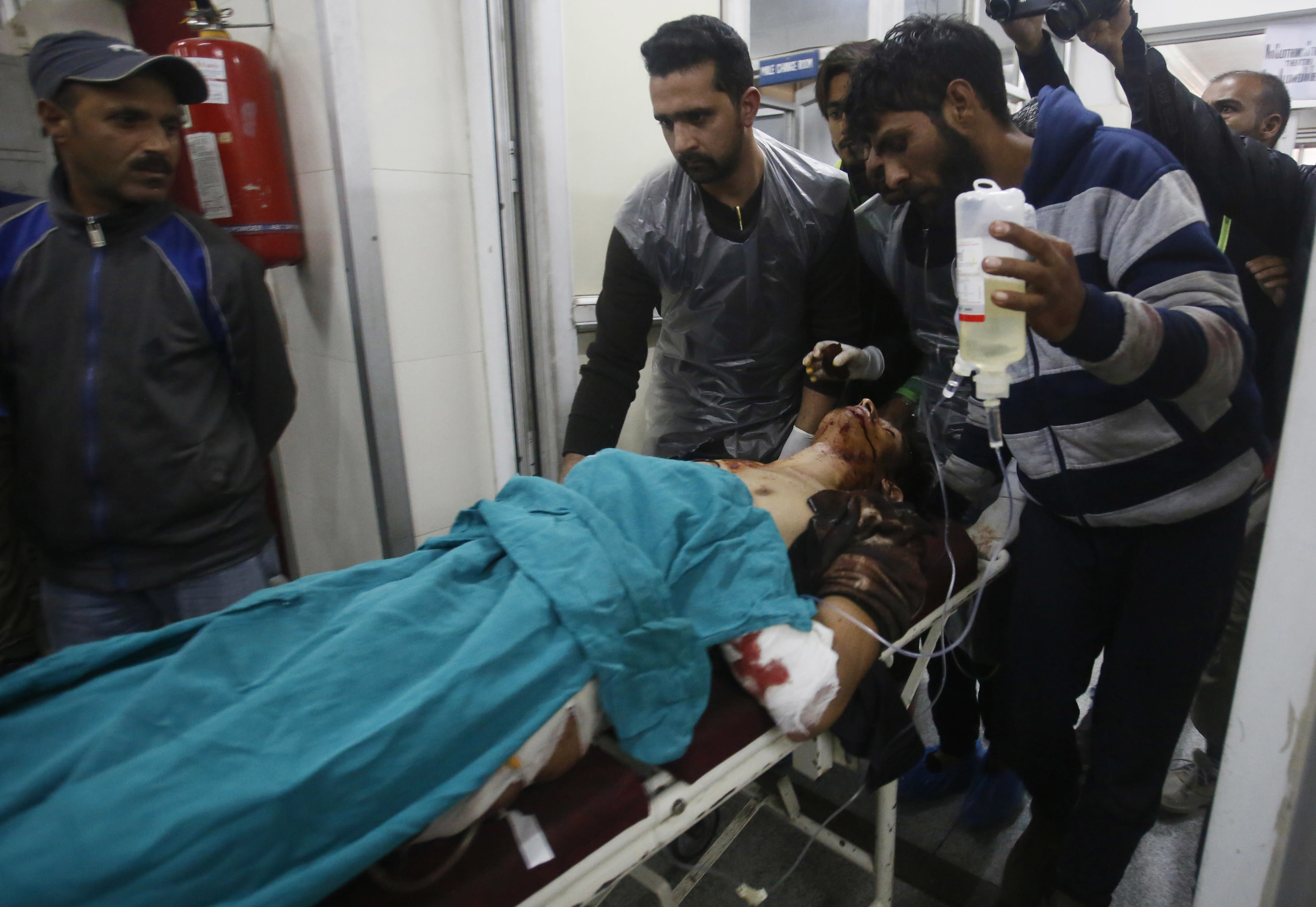 Kashmiri men take an injured civilian on a stretcher inside a hospital in Srinagar, Indian controlled Kashmir, Sunday, Oct. 21, 2018. Three suspected rebels were killed in a gun battle with Indian government forces in disputed Kashmir on Sunday, and at least three civilians were killed in an explosion at the site after the fighting was over, officials and residents said. (AP Photo/Mukhtar Khan)