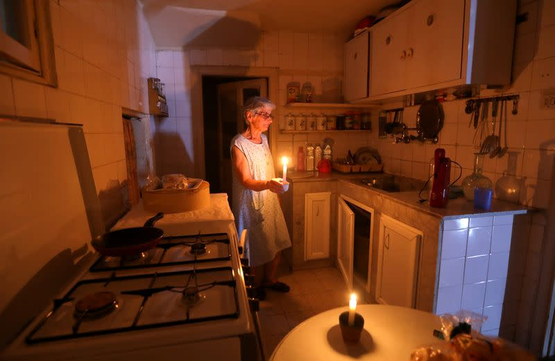 Samira Hanna,70, walks in her kitchen as she holds a candle due to a power cut, in Beirut