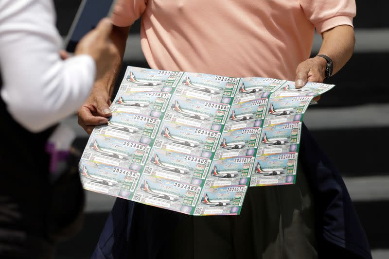 A person holds lottery tickets for the raffle of a presidential luxury jet, organised by the Mexico's government to raise money equivalent to the value of the airplane, outside the National Lottery building in Mexico City