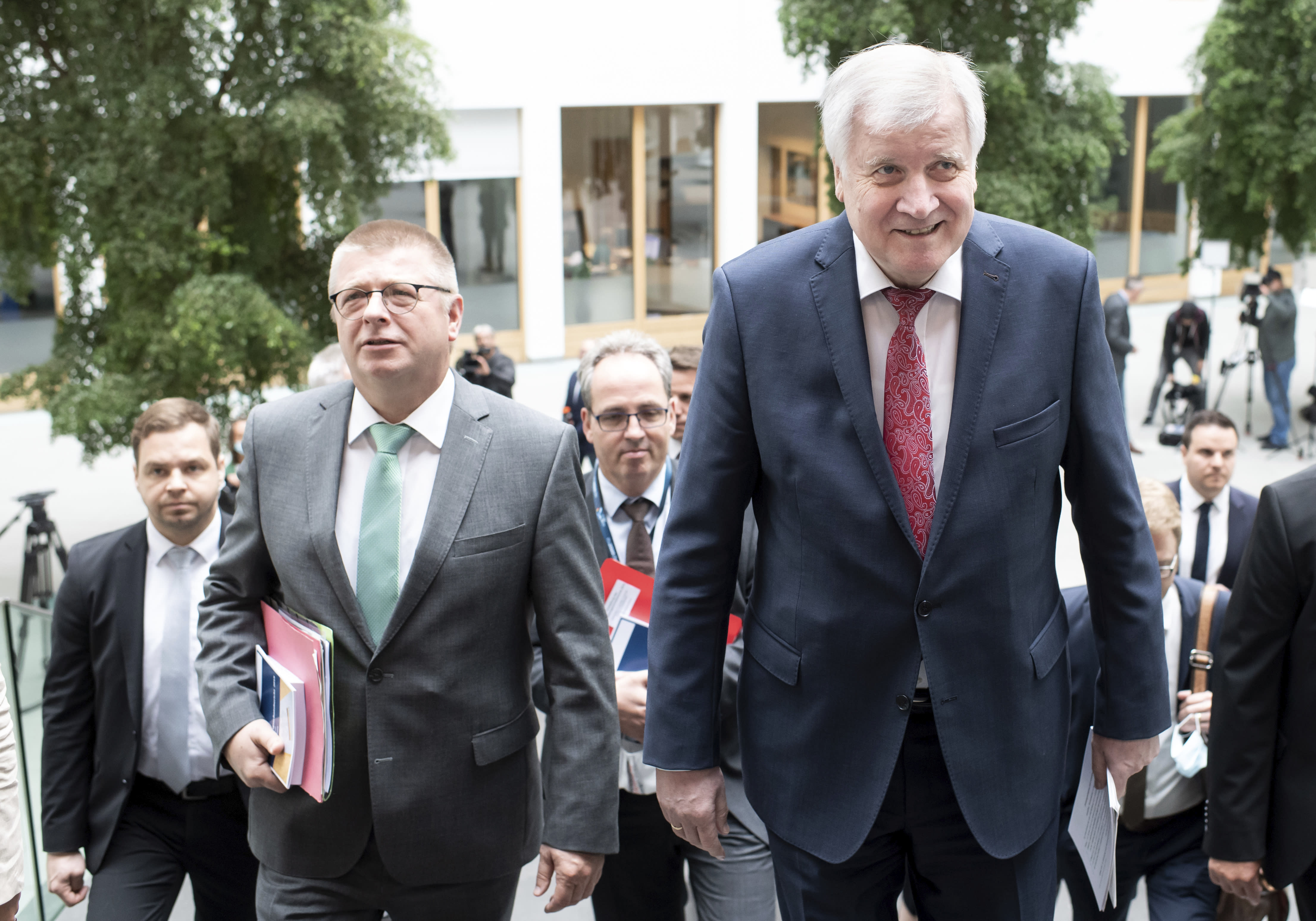 Horst Seehofer (CSU), Federal Minister of the Interior, Homeland and Construction, and Thomas Haldenwang, President of the Federal Office for the Protection of the Constitution (BfV), from right, come to the presentation of the 2019 Report on the Protection of the Constitution at the Federal Press Conference. (Bernd von Jutrczenka/dpa via AP)