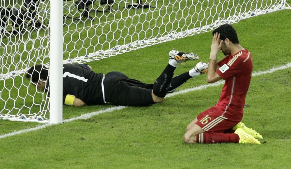 Spain's Sergio Busquets, right, holds his head after failing to score past Chile's goalkeeper Claudio Bravo during the group B World Cup soccer match between Spain and Chile at the Maracana Stadium in Rio de Janeiro, Brazil, Wednesday, June 18, 2014