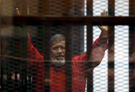 Deposed President Mohamed Mursi greets his lawyers and people from behind bars at a court wearing the red uniform of a prisoner sentenced to death, during his court appearance with Muslim Brotherhood members on the outskirts of Cairo