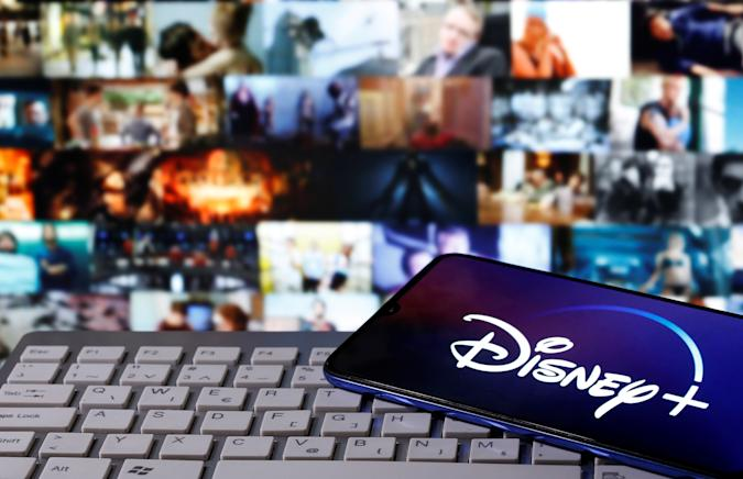 """A smartphone with displayed """"Disney"""" logo is seen on the keyboard in this illustration taken March 24, 2020. REUTERS/Dado Ruvic"""