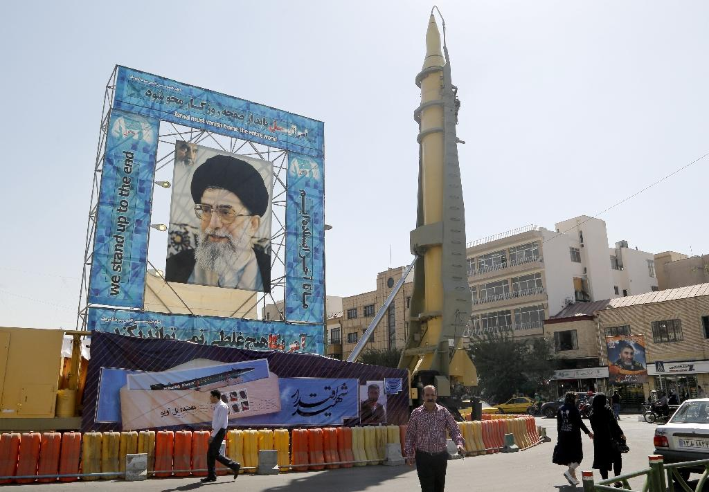 A Ghadr-F missile is displayed next to a portrait of Iran's Supreme Leader Ayatollah Ali Khamenei at a war exhibition at Baharestan square in Tehran in 2016 (AFP Photo/ATTA KENARE)