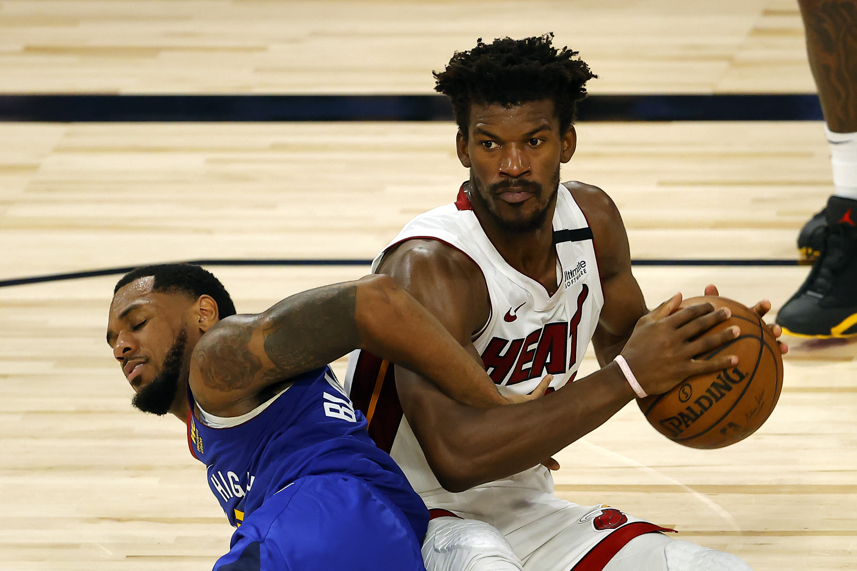 Denver Nuggets' Monte Morris tangles for the ball against Miami Heat's Jimmy Butler during an NBA basketball game, Saturday, Aug. 1, 2020, in Lake Buena Vista, Fla. (Kevin C. Cox/Pool Photo via AP)