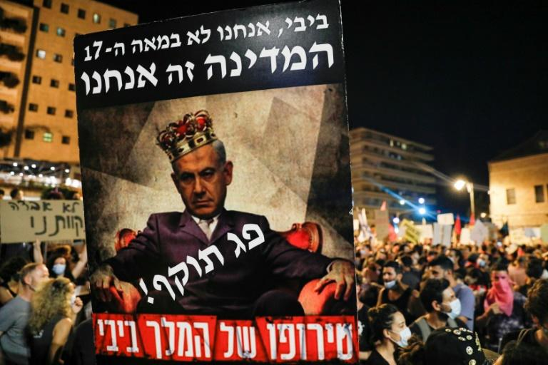 "Anti-Netanyahu protesters hold up a poster showing the Israeli prime minister wearing a crown and the Hebrew words for ""expired"" written across his chest (AFP Photo/Ahmad GHARABLI)"