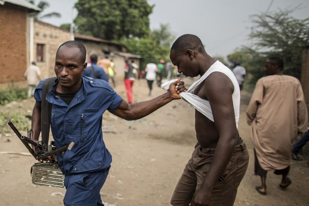A man is detained by a Burundi policeman during a scuffle with residents angered by a search operation in the of the Cibitoke neighbourhood of Bujumbura on June 27, 2015