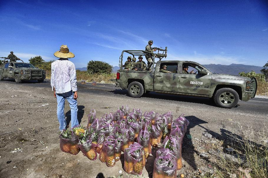 Mexican soldiers stand guard at a checkpoint at the entrance of the Apatzingan community in the state of Michoacan, Mexico on January 12, 2015 (AFP Photo/Alfredo Estrella)