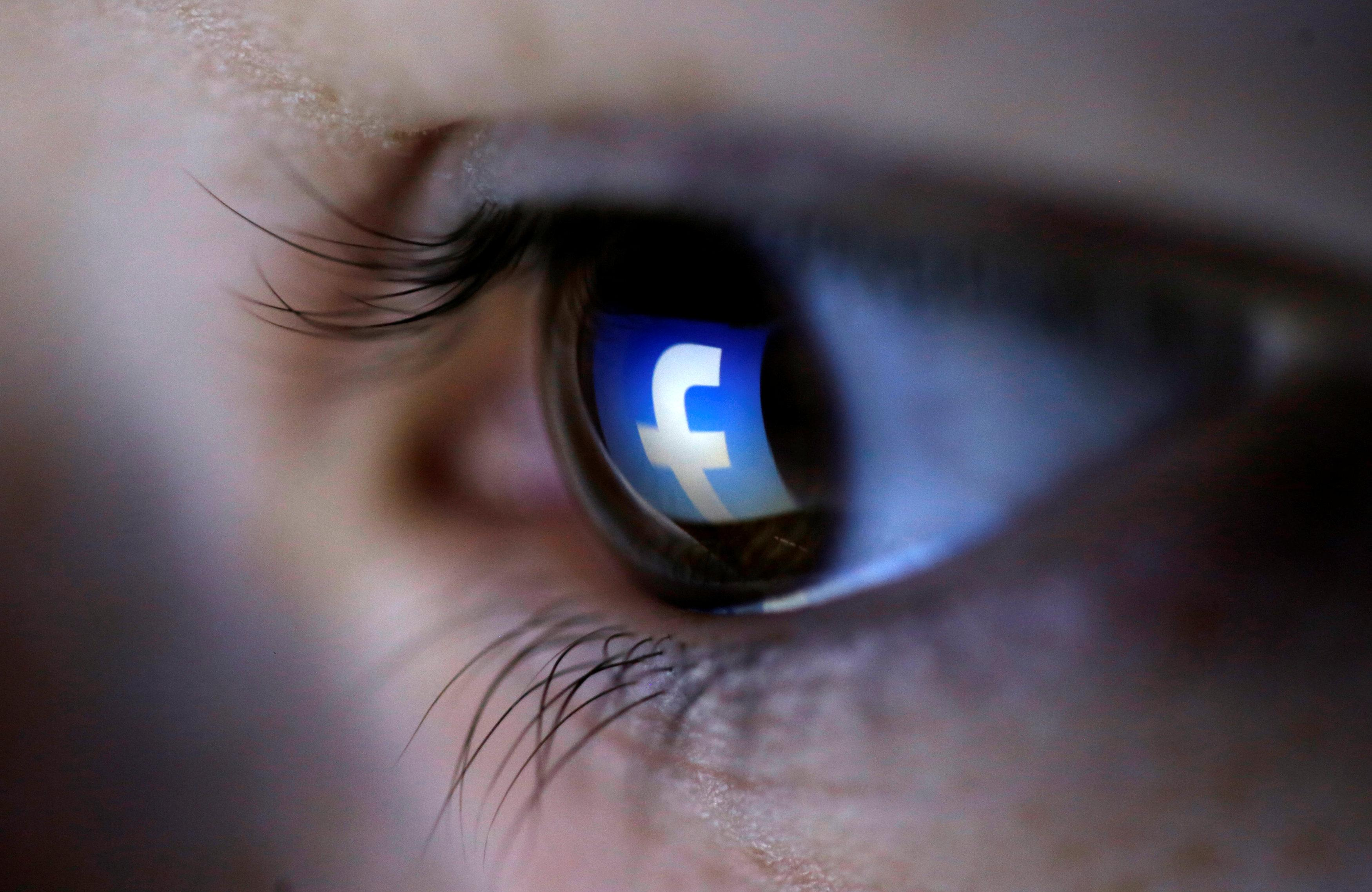 A Facebook logo reflected in a person's eye. REUTERS/Dado Ruvic