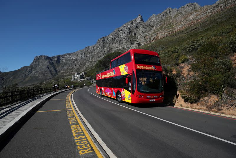 FILE PHOTO: An almost empty tour bus drives below the city's iconic landmark Table Mountain in Cape Town