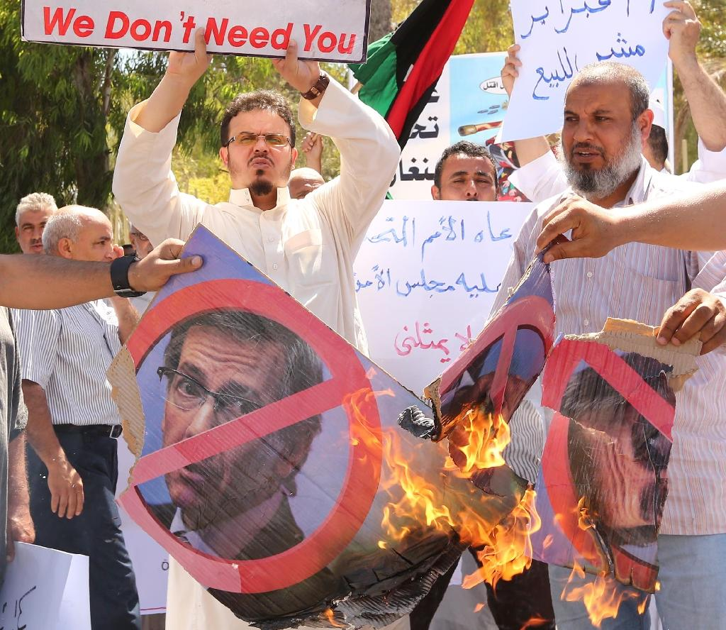 Libyan protesters burn portraits of United Nations envoy Bernardino Leon during a demonstration outside the General National Congress in Tripoli on July 1, 2015 (AFP Photo/Mahmud Turkia)