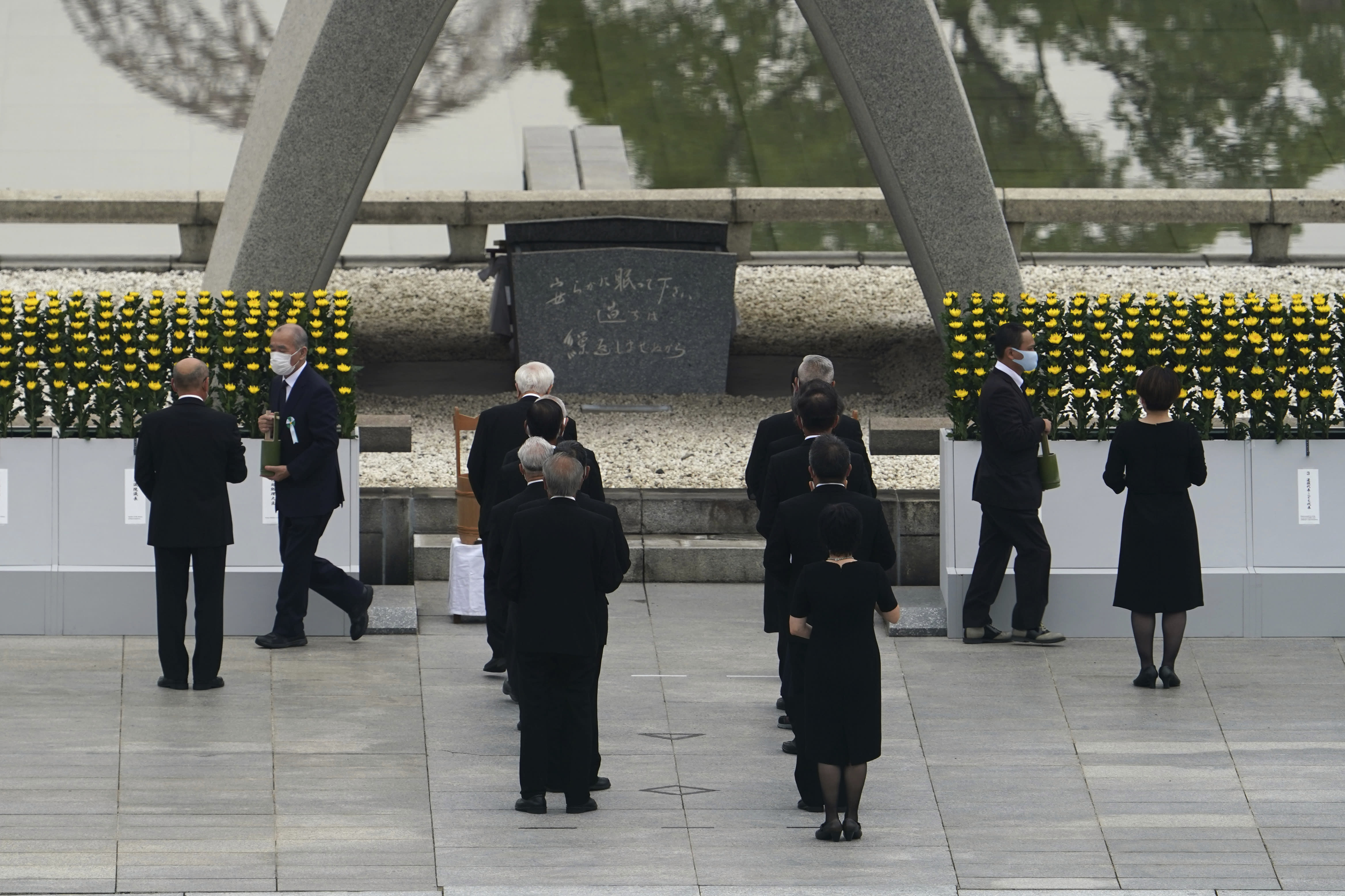 Participants gather at Hiroshima Memorial Cenotaph during the ceremony to mark the 75th anniversary of the bombing at the Hiroshima Peace Memorial Park in Hiroshima, western Japan Thursday, Aug. 6, 2020. (AP Photo/Eugene Hoshiko)