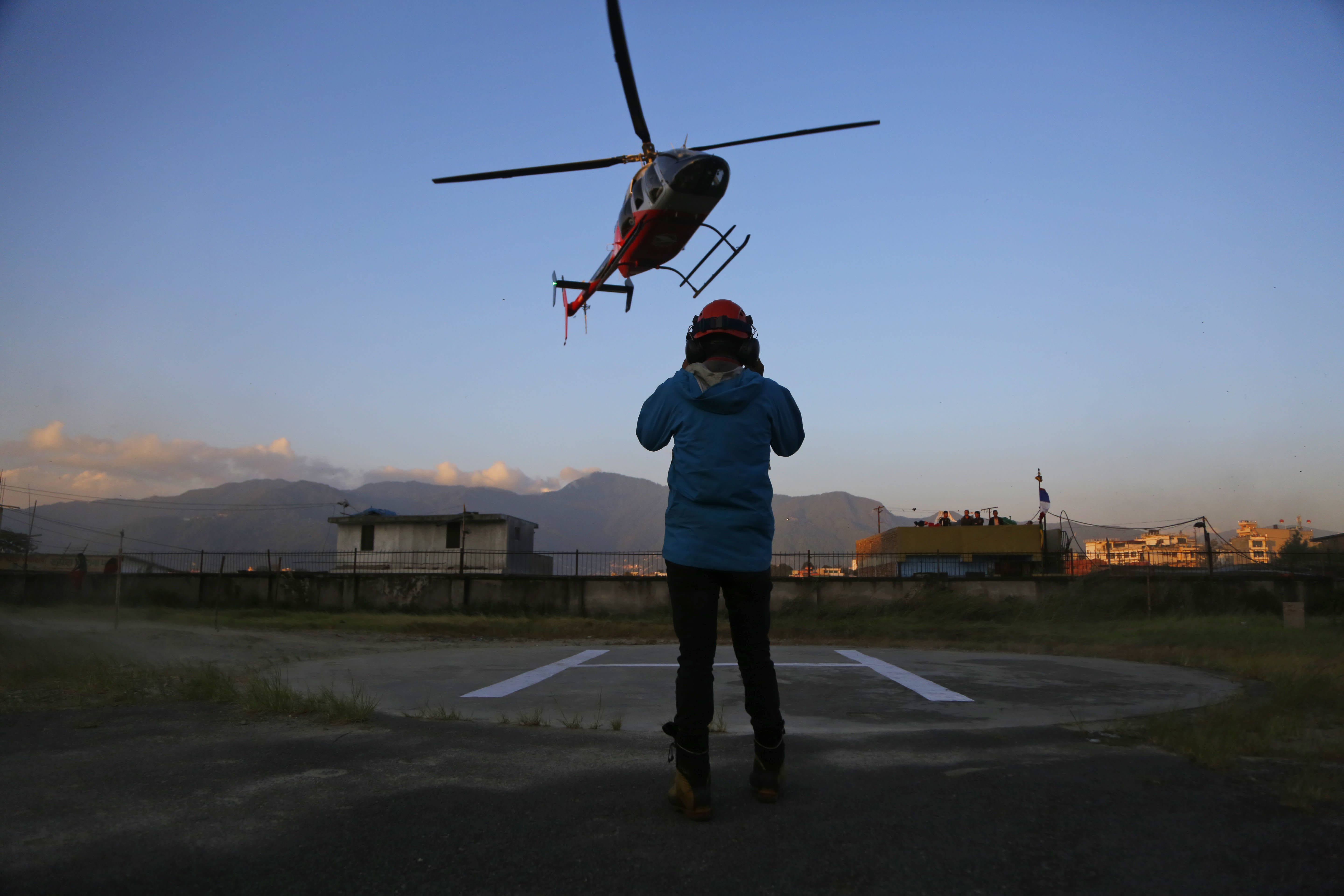 A helicopter carrying bodies of those killed in Gurja Himal mountain arrives at the Teaching hospital in Kathmandu, Nepal, Sunday, Oct. 14, 2018. Rescuers retrieved the bodies of five South Korean climbers and their four Nepalese guides from Gurja Himal mountain, where they were killed when their base camp was swept by a strong storm. (AP Photo/Niranjan Shrestha)