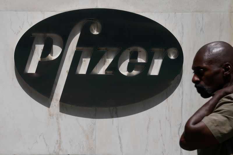 FILE PHOTO: A man walks past a sign outside Pfizer Headquarters in the Manhattan borough of New York City
