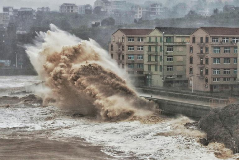 Waves hit a sea wall in Taizhou, China. The same oceans that nourished human evolution are poised to unleash misery on a global scale unless the carbon pollution is brought to heel (AFP Photo/-)
