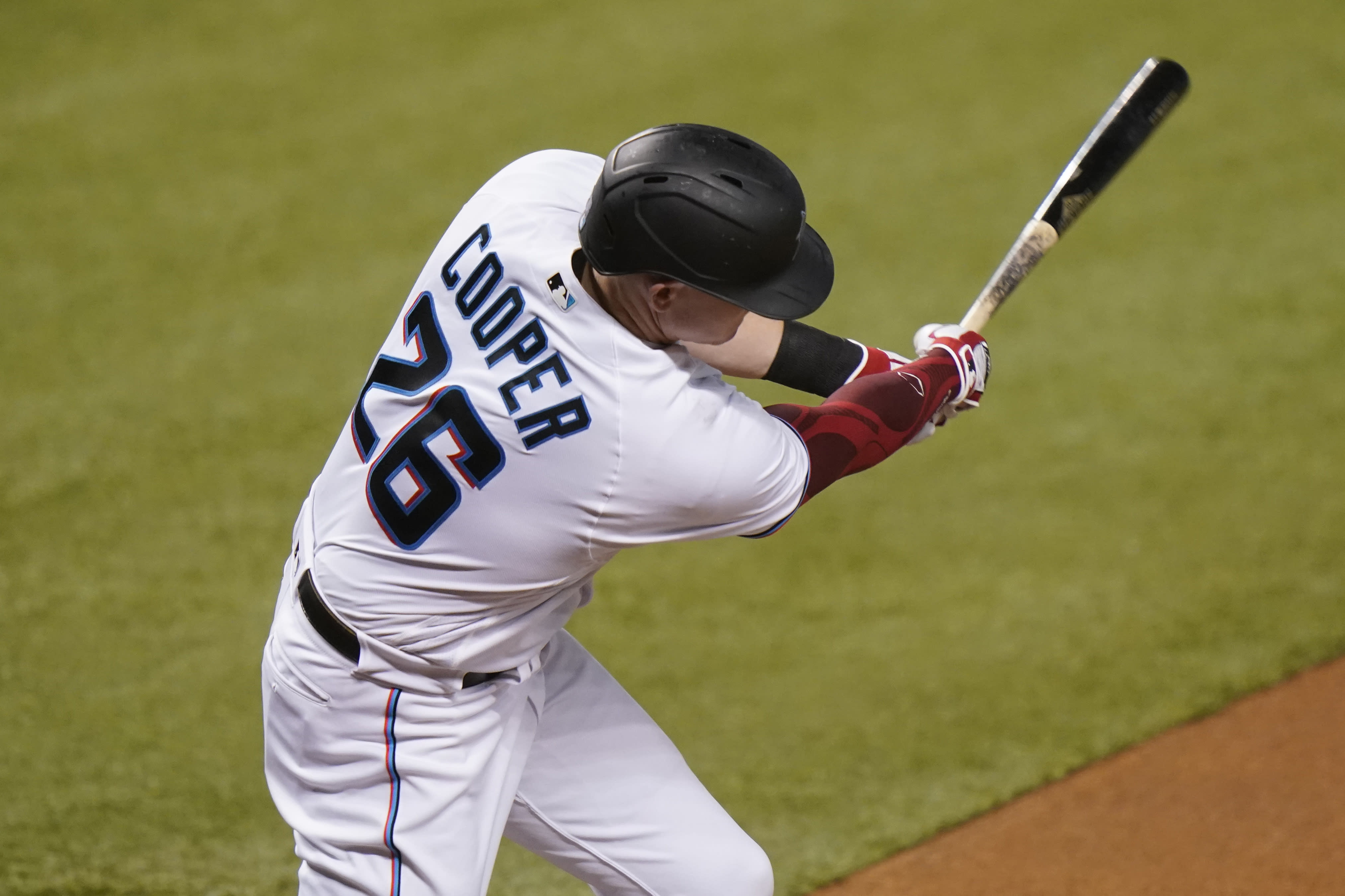 Miami Marlins' Garrett Cooper (26) hits a two-run home run during the first inning of a baseball game against the Boston Red Sox, Wednesday, Sept. 16, 2020, in Miami. (AP Photo/Lynne Sladky)