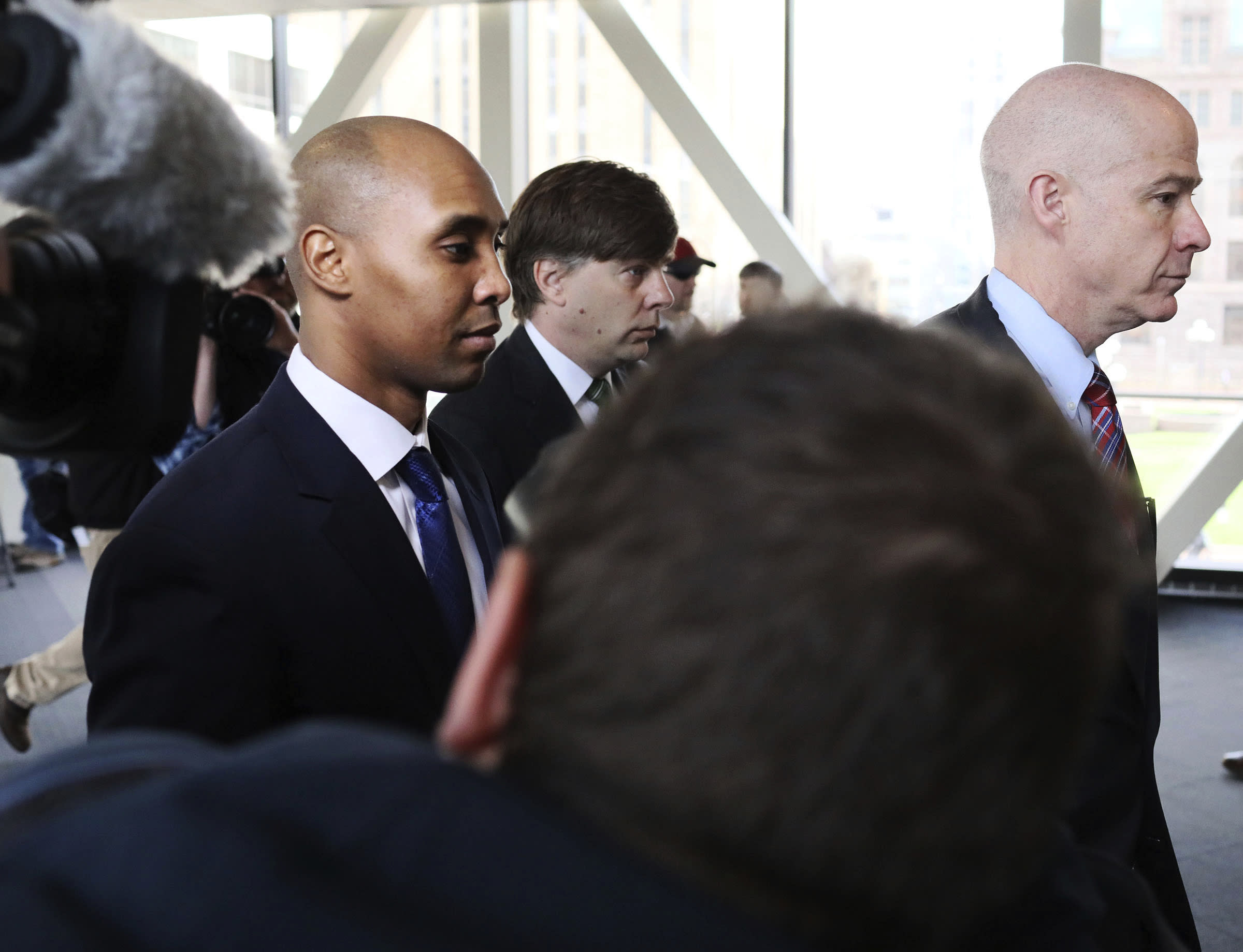 Former Minneapolis police officer Mohamed Noor, center, is accompanied by his attorneys Peter Wold, not pictured, and Thomas Plunkett, right, as he walks towards the Hennepin County Government Center for opening arguments of his trial Tuesday, April 9, 2019, in Minneapolis, Minn. Opening arguments scheduled to begin in the trial of former Minneapolis police officer Mohamed Noor in the shooting death of Justine Ruszczyk Damond. (David Joles/Star Tribune via AP)