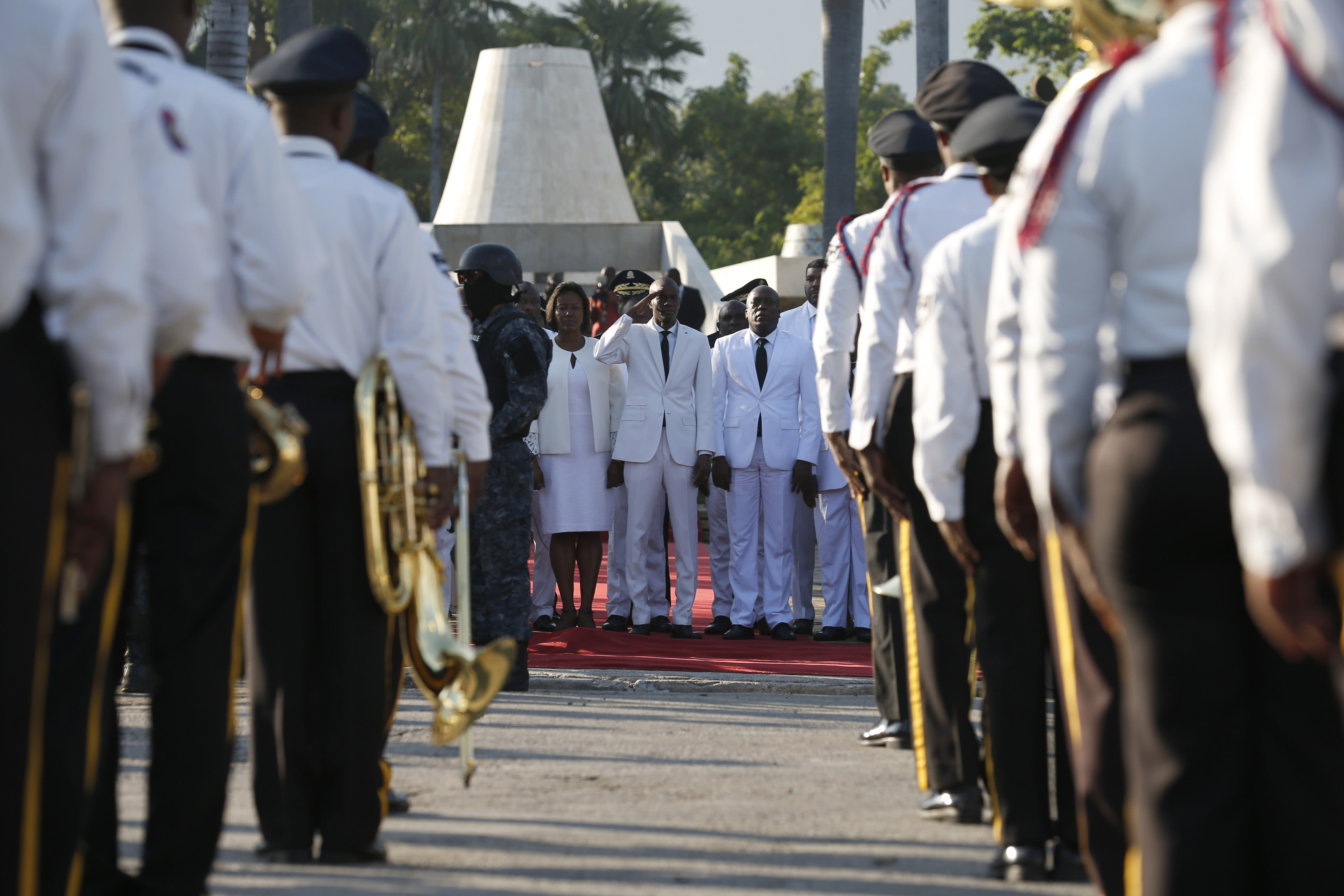 Accompanied by First Lady Martine Moise, center left, President Jovenel Moise salutes a police marching band before laying flowers to mark the anniversary of the death of Haitian revolution leader Jean Jacques Dessalines, at Champ de Mars, adjacent to the National Palace, in Port-au-Prince, Haiti, Thursday Oct. 17, 2019. President Moise has been facing ever more violent protests demanding his resignation fueled by anger over corruption, inflation and dwindling of basic supplies, including gasoline. (AP Photo/Rebecca Blackwell)