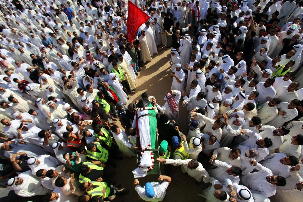 Mourners carry the body of one of the victims of the Al-Imam Al-Sadeq mosque bombing, during a mass funeral at Jaafari cemetery in Kuwait City on June 27, 2015 (AFP Photo/Yasser Al-Zayyat)