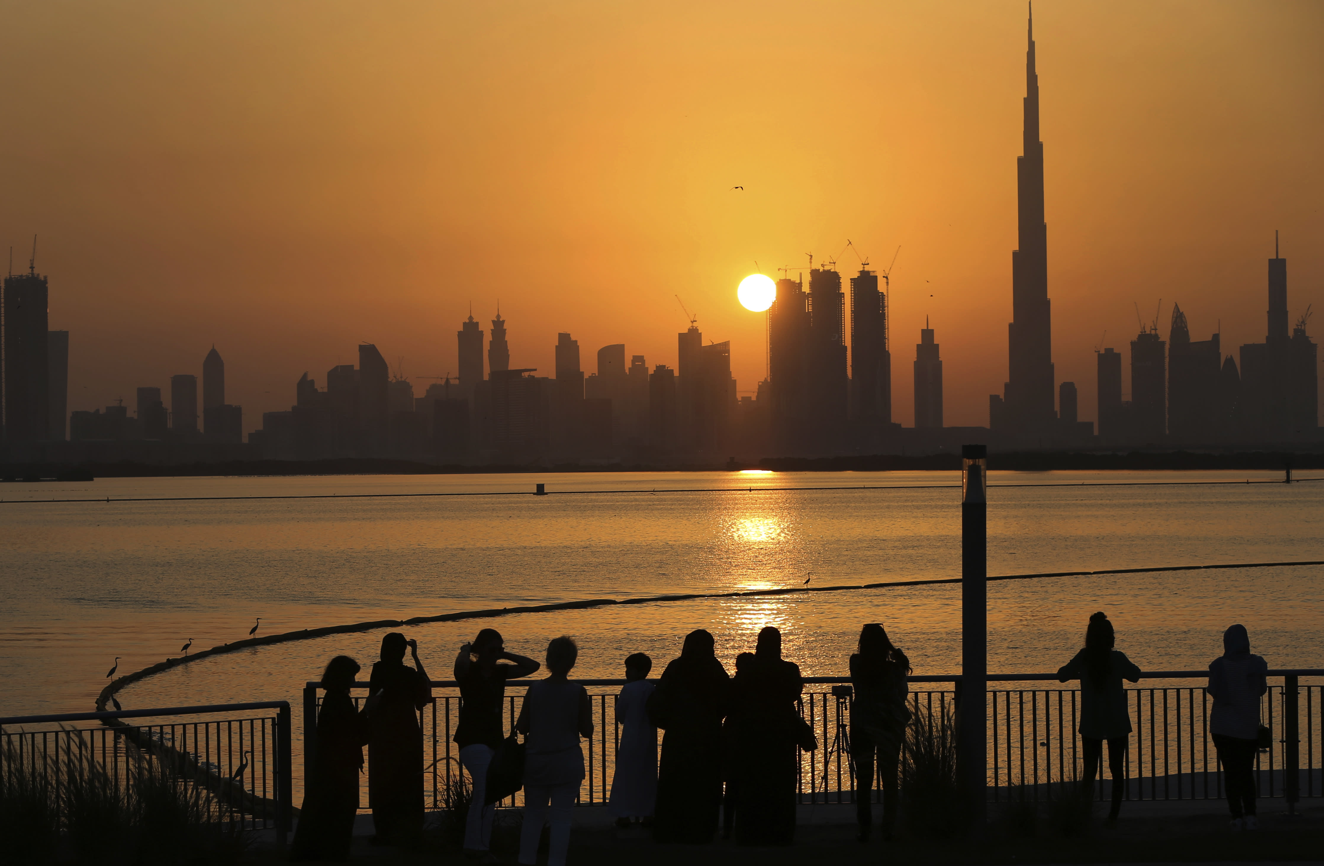 """In this Oct. 7, 2016 file photo, people watch the sunset over the skyline, with Burj Khalifa at right, in Dubai, United Arab Emirates. The United Arab Emirates announced on Saturday a major overhaul of the country's Islamic personal laws, allowing unmarried couples to cohabitate, loosening alcohol restrictions and criminalizing so-called """"honor killings."""" (AP Photo/Kamran Jebreili, File)"""