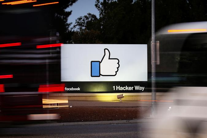 The entrance sign to Facebook headquarters is seen through two moving buses in Menlo Park, California, on Wednesday, October 10, 2018. REUTERS/Elijah Nouvelage