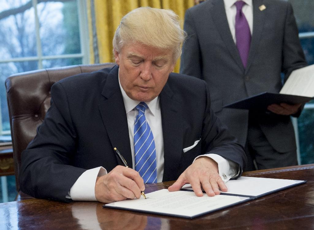 US President Donald Trump signs an executive order withdrawing the US from the Trans-Pacific Partnership in the Oval Office of the White House on January 23, 2017 (AFP Photo/SAUL LOEB)