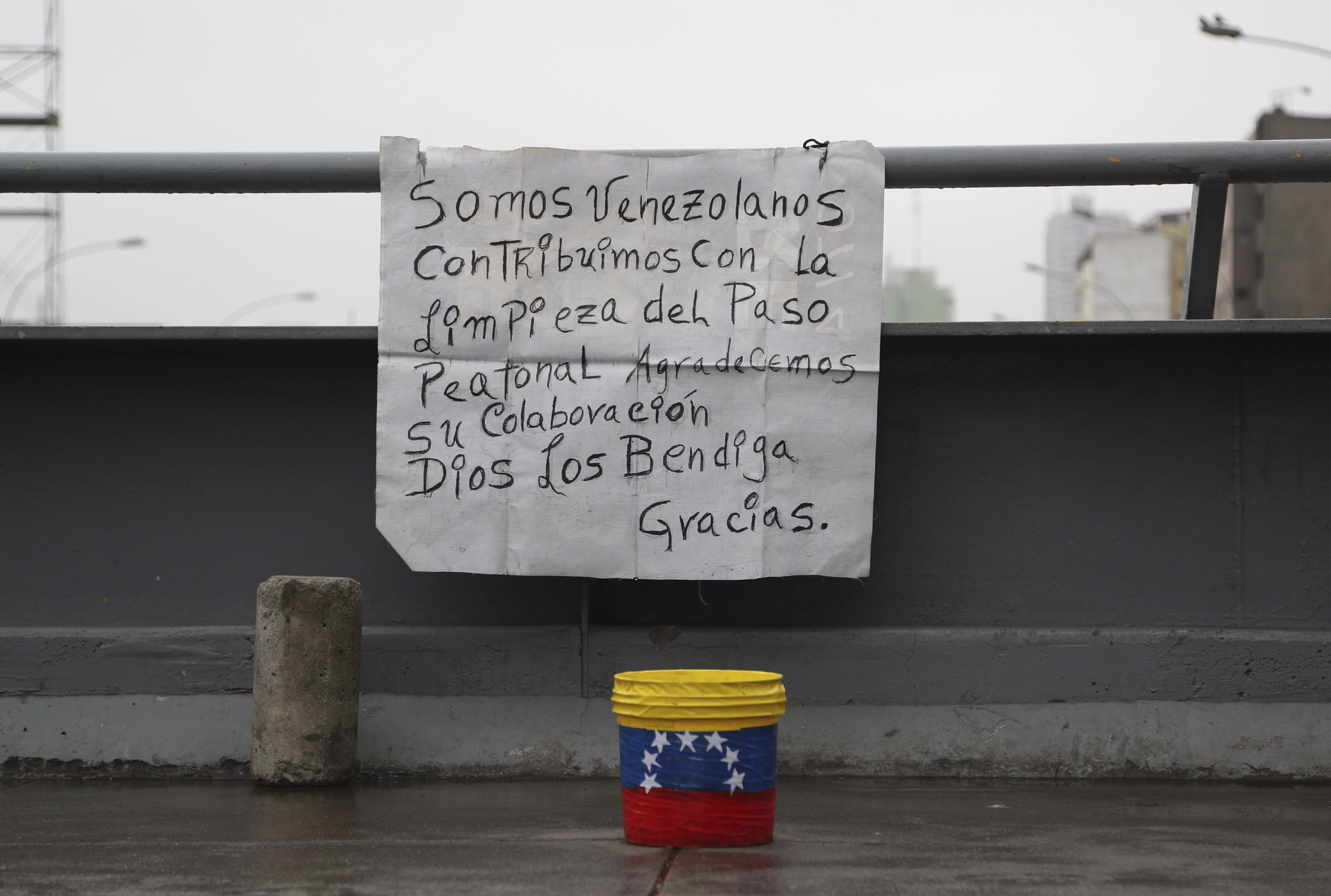 "In this Oct. 8, 201 photo, a sign asking for money in exchange for keeping a bridge clean hangs in Lima, Peru. The sign reads in Spanish ""We are Venezuelans. We contribute to the cleaning of this pedestrian pass. We appreciate your collaboration. May God bless you. Thank you."" (AP Photo/Martin Mejia)"