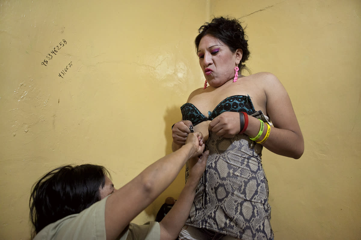 """<p>Evila helps Tamara zip up her dress before leaving to work on the streets. Though her mom visits when she can, Tamara often spends her days alone. """"Sometimes I think about leaving prostitution behind. But, because I'm alone, it's really expensive,"""" said Tamara, who sometimes skip meals in order to pay for her room. (Photo: Danielle Villasana) </p>"""
