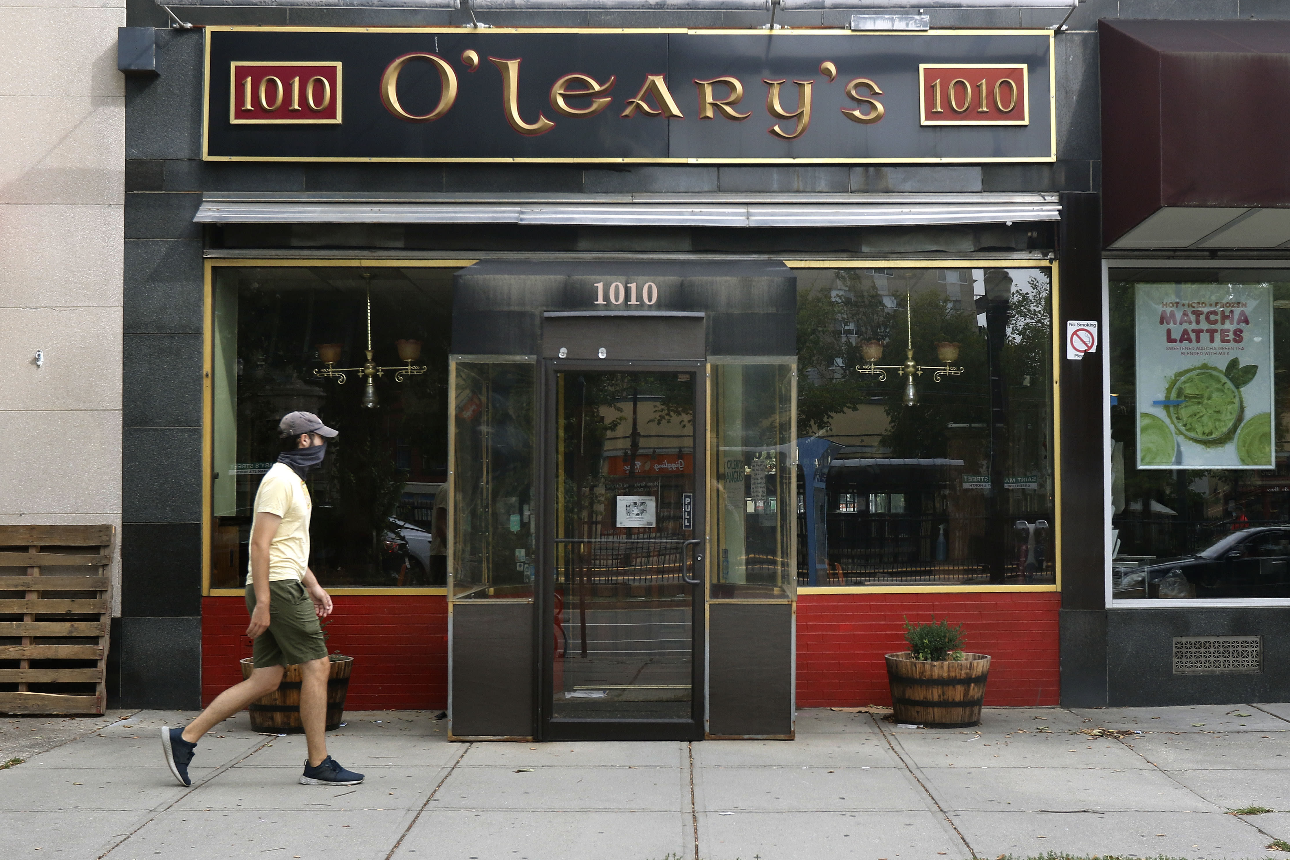 A pedestrian passes by O'Leary's Irish Pub, Tuesday, Aug. 4, 2020, in Brookline, Mass. After being in business for nearly three decades, the pub permanently closed during the coronavirus pandemic. (AP Photo/Bill Sikes)