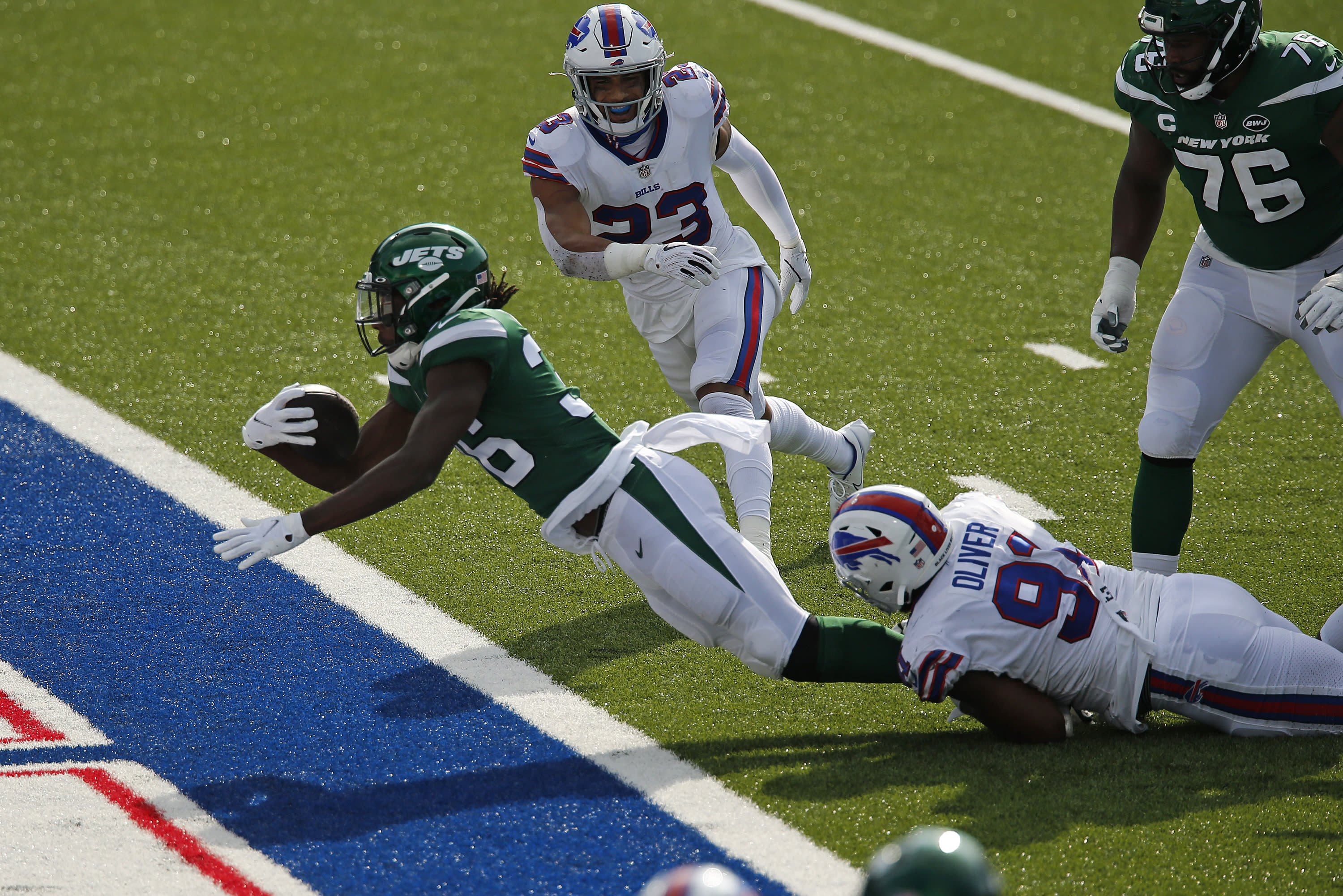 New York Jets running back Josh Adams (36) falls into the endzone for a touchdown while in the grasp of Buffalo Bills defensive tackle Ed Oliver (91) during the second half of an NFL football game in Orchard Park, N.Y., Sunday, Sept. 13, 2020. The Bills won 27-17. (AP Photo/John Munson)