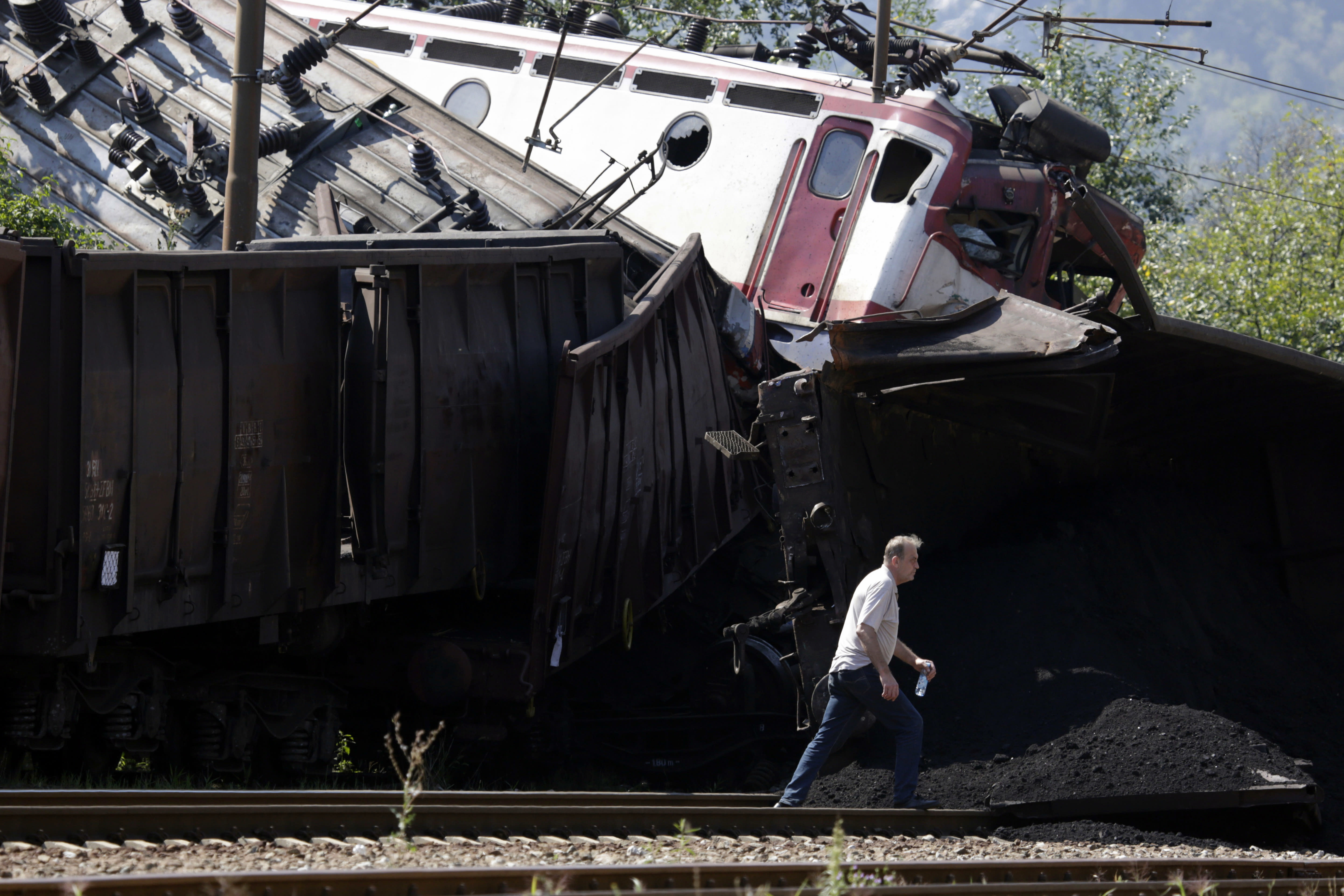 Man walks near the site where two cargo trains collided at the train station in Jablanica, about 80 kms south of Sarajevo, Bosnia, Thursday, Aug. 23, 2018. Police say two people have been killed and one was seriously injured in a head-on freight train collision in southern Bosnia, early Thursday.(AP Photo/Amel Emric)