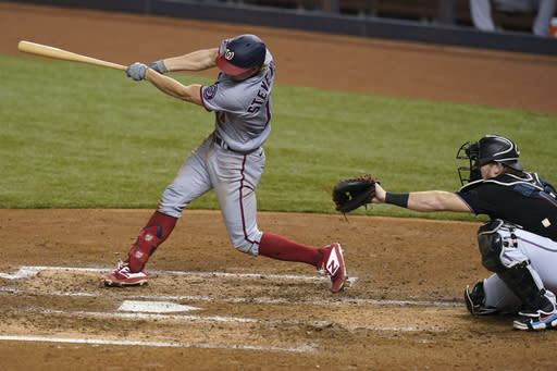 Washington Nationals' Andrew Stevenson hits a two-run single during the fourth inning of the team's baseball game against the Miami Marlins, Saturday, Sept. 19, 2020, in Miami. At right is Marlins catcher Chad Wallach. (AP Photo/Lynne Sladky)