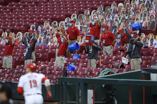 Members of the Cincinnati Reds' grounds crew react as Reds' Joey Votto runs the bases after hitting a two-run home run during the first inning of the team's baseball game against the Milwaukee Brewers in Cincinnati, Wednesday, Sept. 23, 2020. (AP Photo/Aaron Doster)